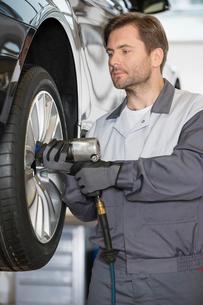Repairman adjusting car's wheel in workshopの写真素材 [FYI03800988]