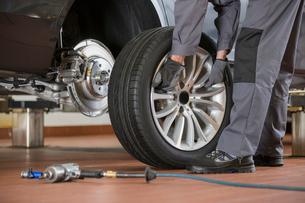 Low section of male mechanic repairing car's tire in repair shopの写真素材 [FYI03800989]