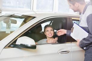 Smiling female customer receiving car key from mechanic in workshopの写真素材 [FYI03800997]