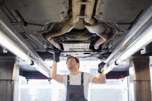 Mid adult male repair worker repairing car in workshopの写真素材 [FYI03800998]