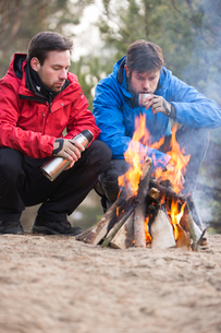 Male backpackers having coffee at campfire in forestの写真素材 [FYI03801015]
