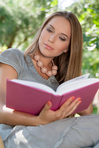 Attractive young woman reading book in parkの写真素材 [FYI03801036]