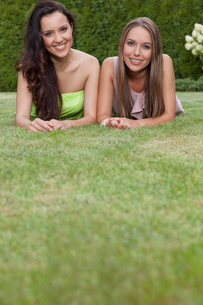 Portrait of attractive young female friends relaxing in parkの写真素材 [FYI03801046]