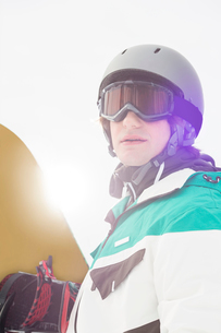 Handsome young man holding snowboard outdoorsの写真素材 [FYI03801066]