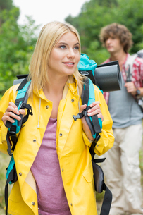 Female backpacker with man standing in background at forestの写真素材 [FYI03801071]
