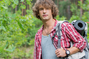 Young male hiker with backpack looking away in forestの写真素材 [FYI03801072]