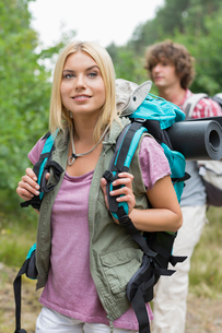Beautiful female backpacker looking away with man standing in background at forestの写真素材 [FYI03801073]