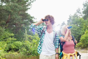 Young couple using binoculars while hiking in forestの写真素材 [FYI03801074]