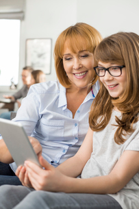 Happy mother and daughter using tablet PC with family sitting in background at homeの写真素材 [FYI03801085]