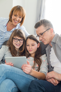Family using digital tablet together in living roomの写真素材 [FYI03801088]