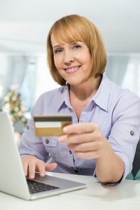 Portrait of happy woman shopping online at home during Christmasの写真素材 [FYI03801097]