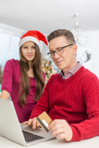 Portrait of father and daughter shopping online during Christmasの写真素材 [FYI03801100]