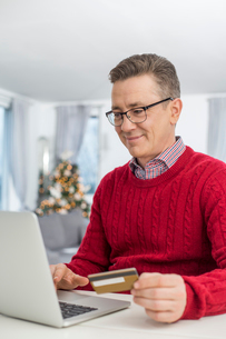 Smiling man using credit card and laptop to shop online at home during Christmasの写真素材 [FYI03801101]