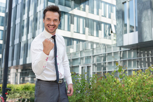 Portrait of happy businessman with clenched fist standing outside office buildingの写真素材 [FYI03801116]