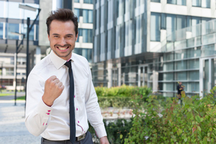 Portrait of cheerful businessman with clenched fist standing outside office buildingの写真素材 [FYI03801118]