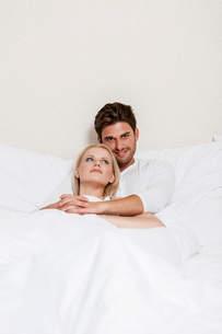 Portrait of happy young man with woman relaxing in bedの写真素材 [FYI03801123]