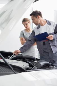 Male maintenance engineer explaining car engine to female customer in repair shopの写真素材 [FYI03801144]