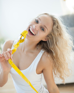 Portrait of woman laughing while holding fork wrapped with measuring tapeの写真素材 [FYI03801160]