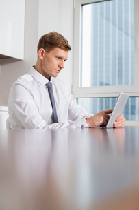 Mid adult businessman using tablet computer at kitchen tableの写真素材 [FYI03801175]