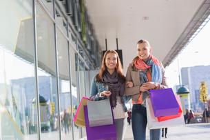 Happy female friends with shopping bags walking on sidewalkの写真素材 [FYI03801193]