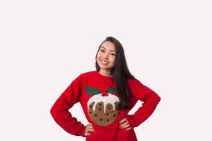 Portrait of woman in Christmas sweater standing with hands on hips over gray backgroundの写真素材 [FYI03801194]