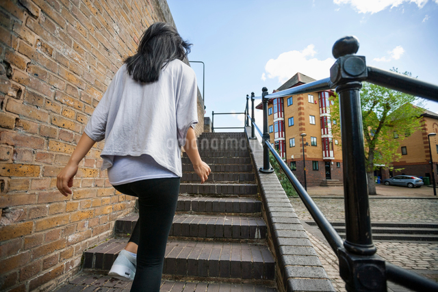 Rear view of young woman walking up stairs outdoorsの写真素材 [FYI03801208]
