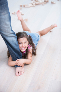 Portrait of happy girl being dragged by father on hardwood floorの写真素材 [FYI03801215]