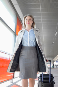 Young businesswoman with luggage walking in railroad stationの写真素材 [FYI03801252]