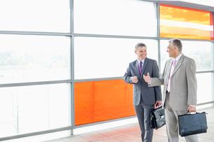 Happy businessmen talking while walking in railroad stationの写真素材 [FYI03801253]