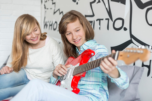 Girl listening to sister playing guitar at homeの写真素材 [FYI03801266]