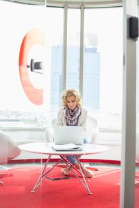 Creative businesswoman using laptop in officeの写真素材 [FYI03801282]