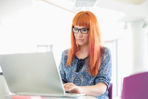 Businesswoman working on laptop in creative officeの写真素材 [FYI03801284]