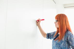 Businesswomen writing on whiteboard in creative officeの写真素材 [FYI03801288]