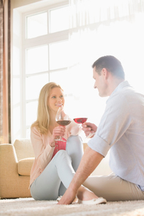 Happy couple looking at each other while having red wine at homeの写真素材 [FYI03801311]