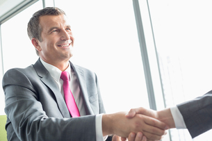 Smiling mature businessman shaking hands with partner in officeの写真素材 [FYI03801346]