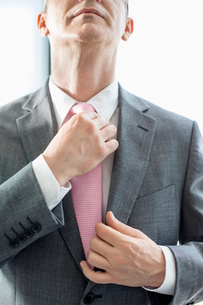 Midsection of mature businessman adjusting tieの写真素材 [FYI03801349]