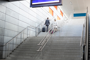 Rear view of businesspeople with luggage moving upstairs in railroad stationの写真素材 [FYI03801360]
