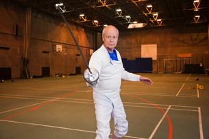 Senior man in fencing suit holding foilの写真素材 [FYI03801462]