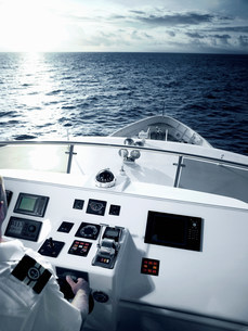 Captain at helm of large motor yachtの写真素材 [FYI03801524]