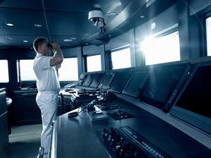 Captain in cockpit of motor yacht, usingの写真素材 [FYI03801526]