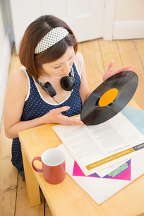 Woman looking at vinyl recordの写真素材 [FYI03801557]