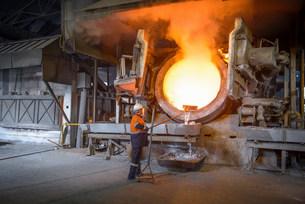 Worker raking liquid aluminum from furnace at recycling planの写真素材 [FYI03801744]