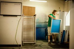 Man holding frame in screen print workshopの写真素材 [FYI03801785]