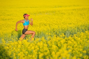 Young woman running in oil seed rape fieldの写真素材 [FYI03801856]