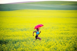 Young woman running in oil seed rape field with red umbrellaの写真素材 [FYI03801858]