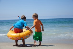 Two young brothers playing with rubber ring at beachの写真素材 [FYI03801860]