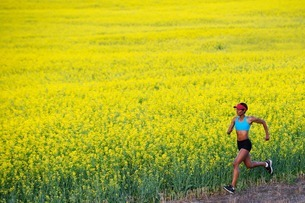 Young woman running next to oil seed rape fieldの写真素材 [FYI03801863]