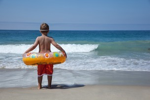 Young boy playing with rubber ring at beachの写真素材 [FYI03801865]