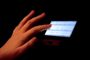 Close up of hand using touchscreen displaying sheet musicの写真素材 [FYI03802008]