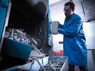 Worker shot blasting springs in laboratoryの写真素材 [FYI03802119]